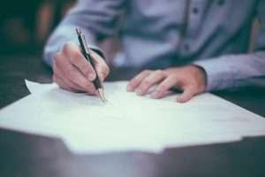 mężczyzna z długopisem, wypełniający dokument